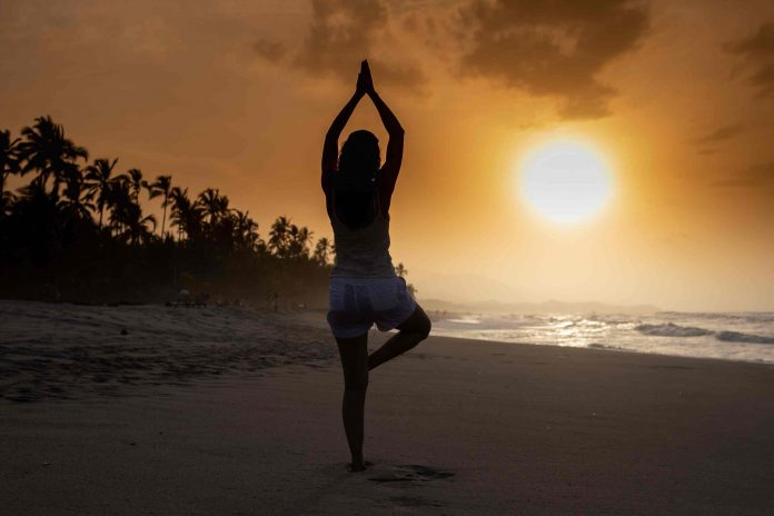 A Woman Posing Yoga Posture on the Beach in the Morning